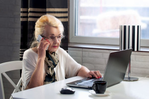 elderly lady talking on the phone and working with computer